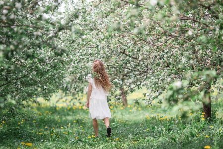 Beautiful little girl in blooming apple tree garden on spring day runing and enjoying the weather